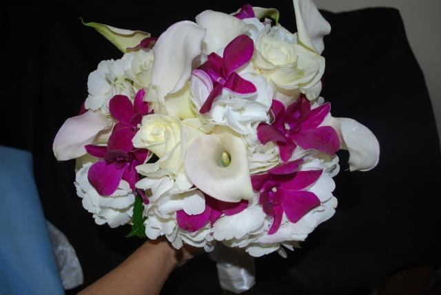 White Hydrangea, Mini Calla Lily, and South American Roses with an accent of Fresh Thailand Dendrobium Orchids in Purple, make this Hand Tied Bouquet most beautiful.
